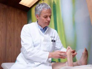 Врач осматривает пациента с невромой